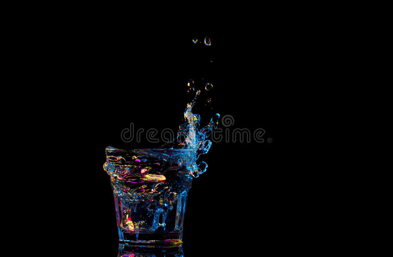 Bright cocktail in glass and splashing water on dark background.  royalty free stock photos