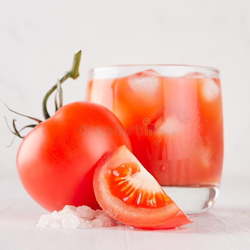 Bright cold red tomato cocktail bloody Mary in elegance glass with tomato, salt, straw, ice and piece on white wooden board. stock photos