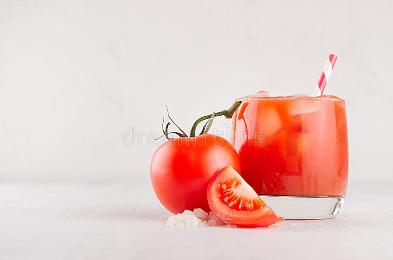 Bright cold red tomato cocktail bloody Mary in elegance glass with glossy tomato, salt, straw, ice, piece on white wooden board. royalty free stock photos