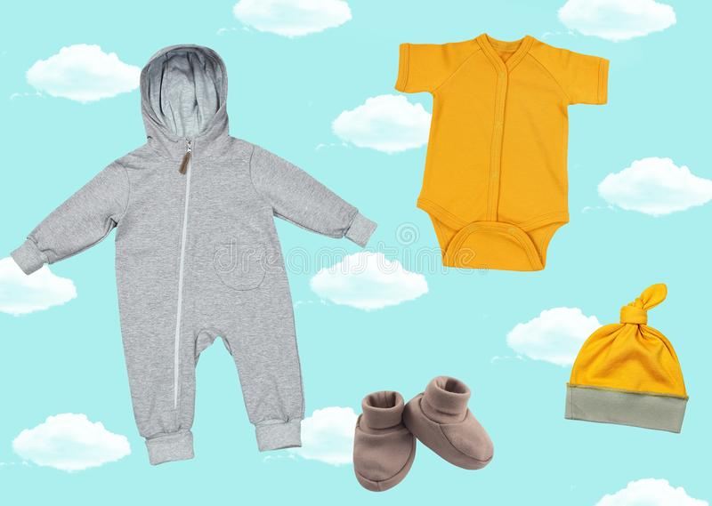 Bright collage with clothes for newborn babies on a blue background with clouds. Cap, booties, jumpsuit and body on a bright background stock photos