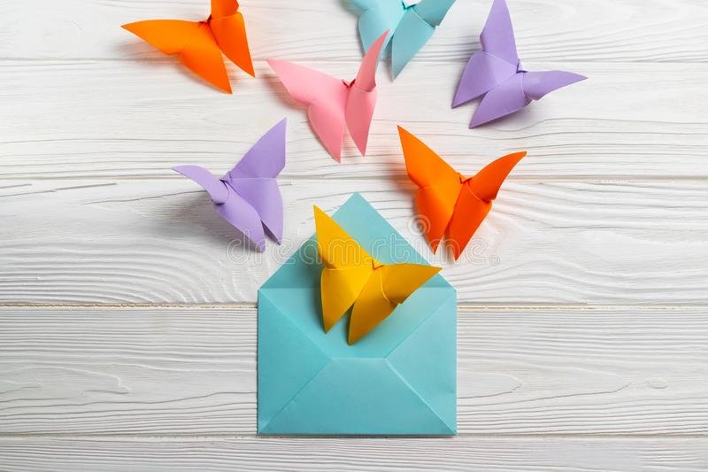 Bright coloful paper butterfiles flying out of the envelope. Greetings card. Overhead flat lay stock photography