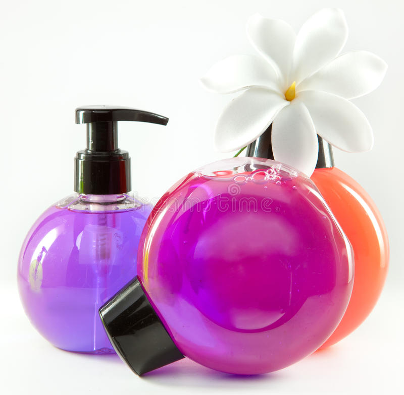 Liquid soap in three multi-colored bottles and white flower royalty free stock image