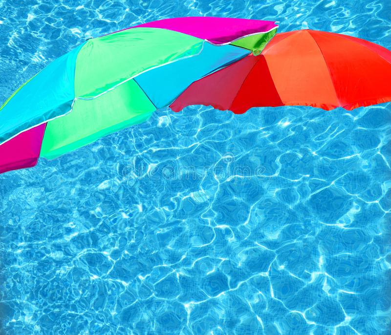Bright color parasols over turquoise blue pool. Water surface background stock photo