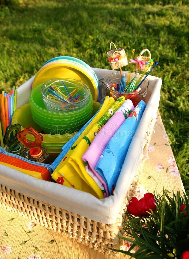 Bright color summer picnic accessories. A basket with bright multicolor summer picnic glass and plastic accessories, plates and things on a lawn, vertical stock photography