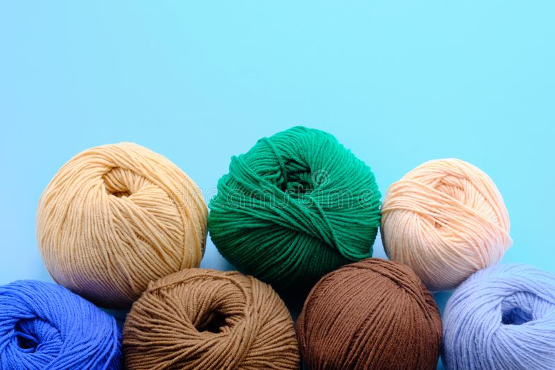 Bright color yarn clews on the blue background. Concept of amigurumi toy making, handycraft, hobbie royalty free stock photos