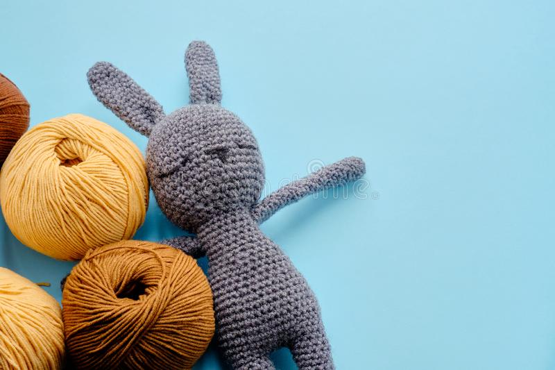 Bright color yarn clews with grey stuffed amigurumi bunny on the blue background. Concept of amigurumi toy making, handycraft,. Bright color yarn clews with gray royalty free stock photography