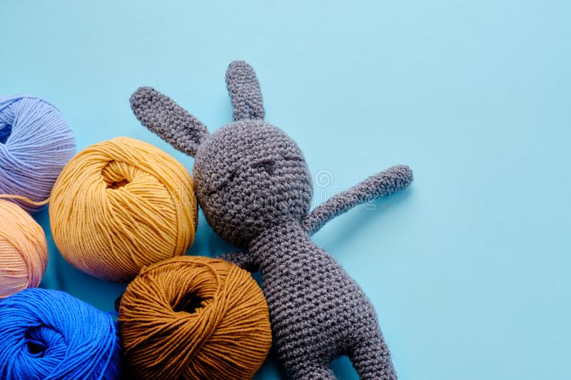 Bright color yarn clews with grey stuffed amigurumi bunny on the blue background. Concept of amigurumi toy making, handcrafting,. Bright color yarn clews with stock photo