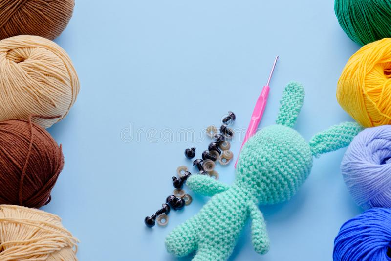 Bright color yarn clews with pastel green stuffed bunny on the blue background. Concept of amigurumi toy making, handycraft,. Knitting, hobbie royalty free stock photo