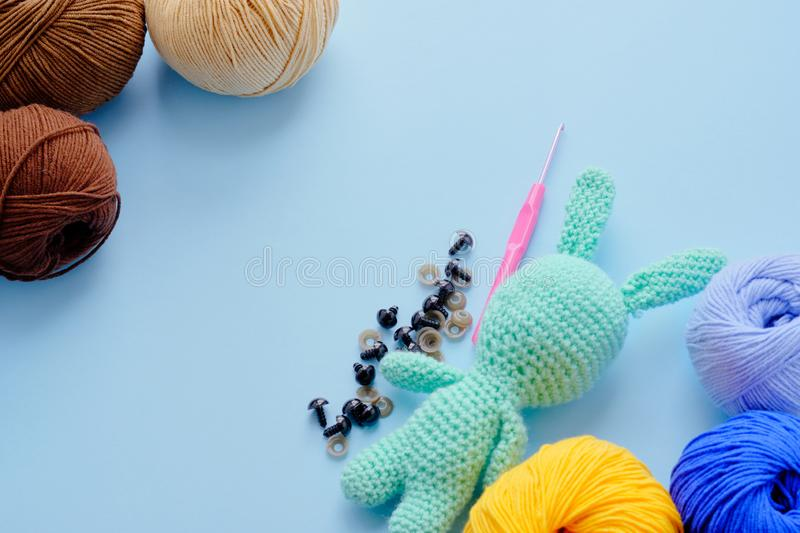 Bright color yarn clews with pastel green stuffed bunny on the blue background. Concept of amigurumi toy making, handycraft,. Knitting, hobbie stock photos