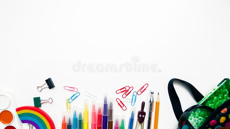 Bright colored backpack and colorful stationary school supplies on white background, space or text flat layer. Concept back to. School. Close-up copy space royalty free stock photography