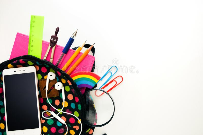 Bright colored backpack, full of school supplies, blank cell phone screen, headphones, pink notebook, glasses. Let`s return to th stock images