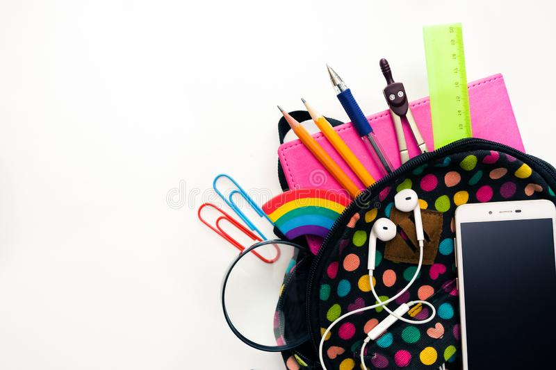Bright colored backpack, full of school supplies, blank cell phone screen, headphones, pink notebook, glasses. Let`s return to th. E school concept. Close-up royalty free stock photography