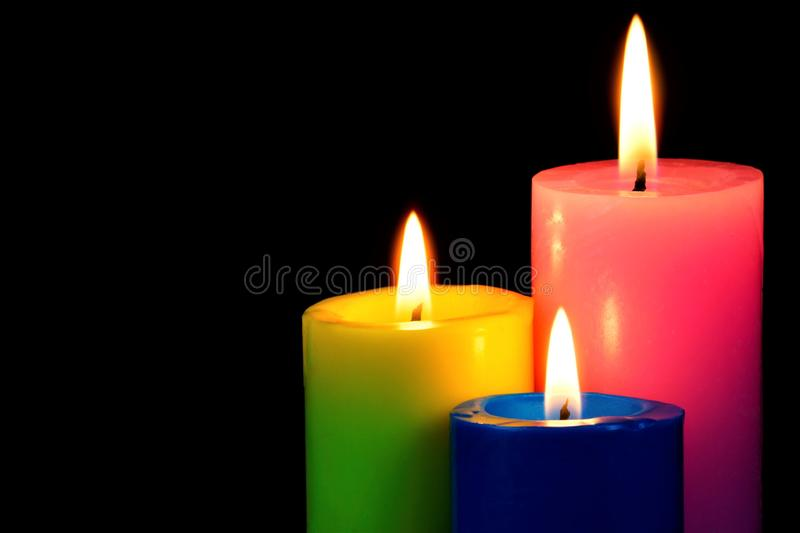 Bright colored candles burning on a black creative background. Candles illuminate, and symbol of faith, hope, love, holiday of stock image