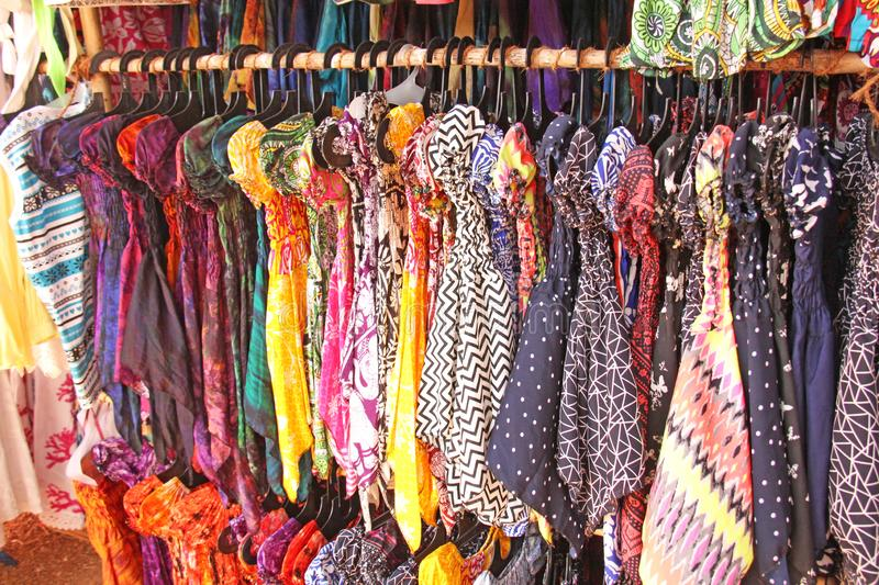 Bright colored children`s dresses or sarafans hang on hangers and are sold in the market of bazaars in India. Showcase with royalty free stock photography