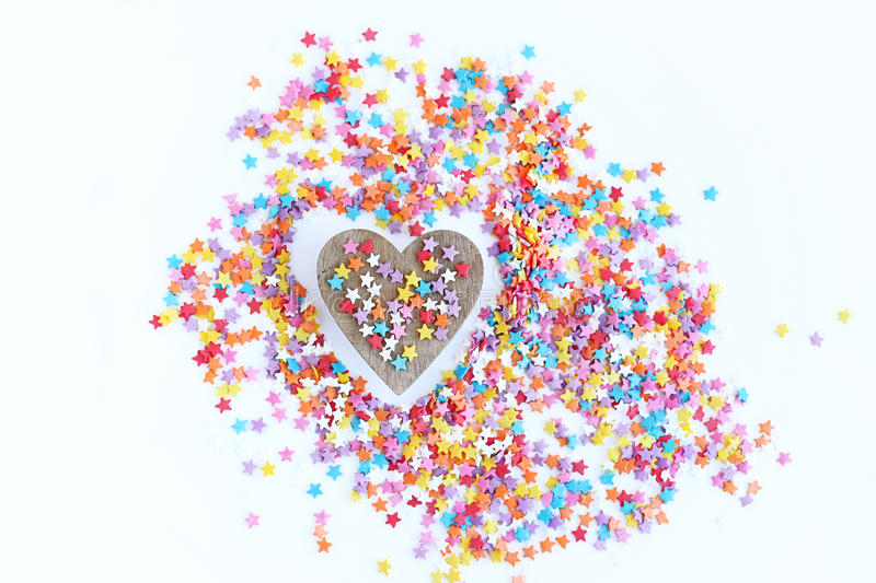 Bright colored confectionery sprinkling of stars and wooden heart on a light background, soft focus, blur. Bright colored confectionery sprinkling of stars and royalty free stock photo