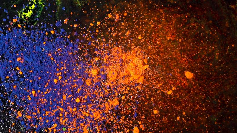 Bright colored dust explosion on a black background, art concept. Motion of blue and orange powder inks, multicolored stock photography