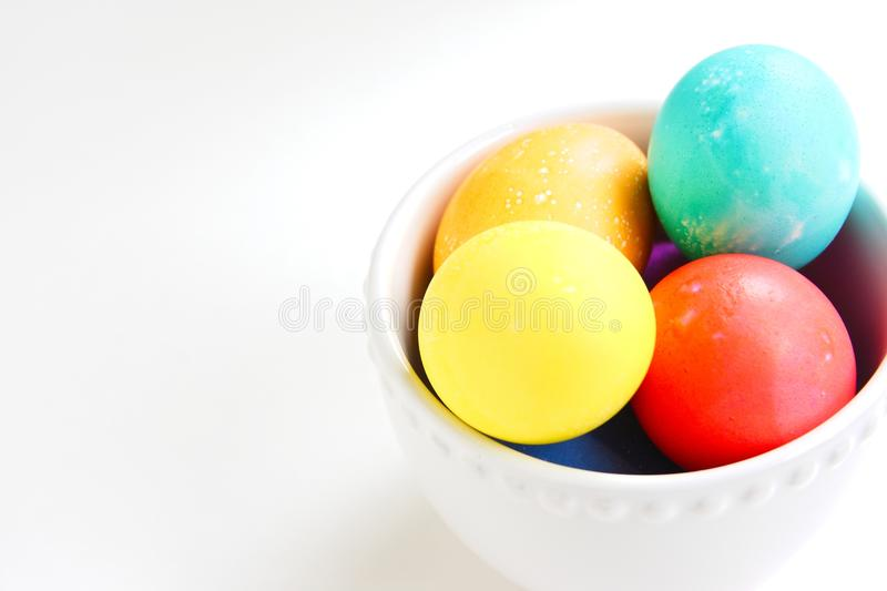 Bright colored Easter eggs nested in a white bowl. royalty free stock image