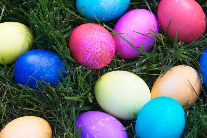 Bright colored Easter eggs piled in the green grass. stock images