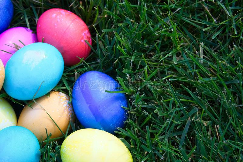 Bright colored Easter eggs piled in the green grass. royalty free stock photography