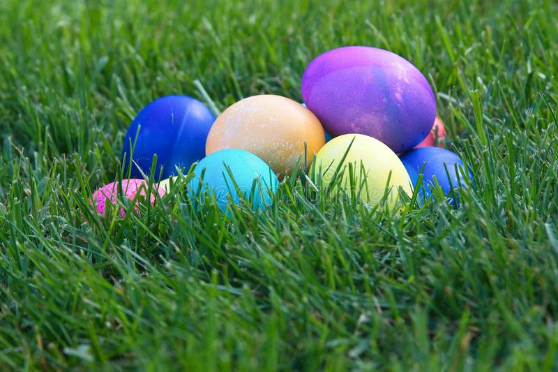 Bright colored Easter eggs piled in the green grass. royalty free stock photo
