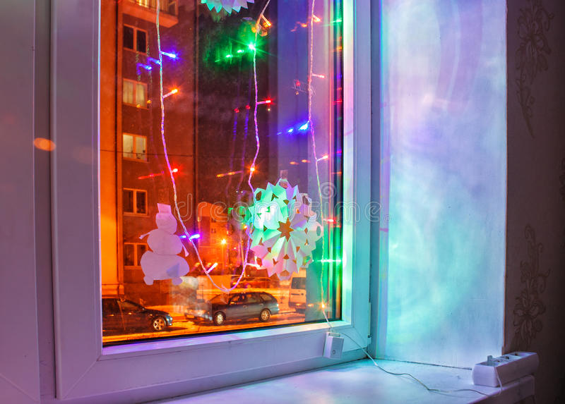 Bright colored electric garland in the window stock photo