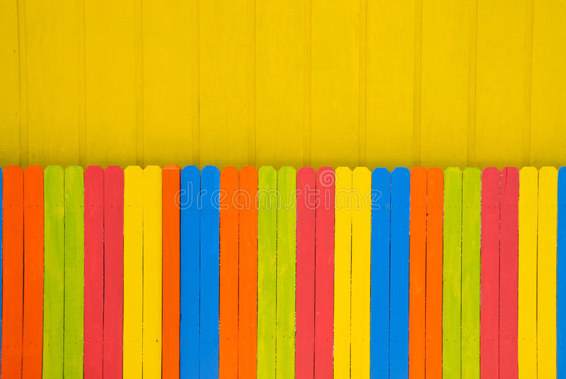 Bright Colored Fence. A brightly colored painted fence against a yellow wall stock image
