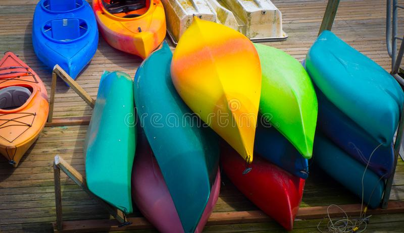 Colorful Kayak piled on dock. Bright colored kayaks canoes and small boats pile on dock awaiting tourists royalty free stock photo