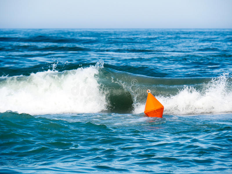 A bright colored orange buoy on an agitated sea. A bright orange buoy marks the area that is safe for swimming royalty free stock photo