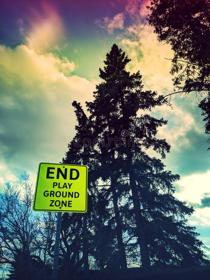Play ground sign outside. Bright colored photo of a sign, end play ground zone, trees and clouds, spring time, trees starting to bloom, local, outside, colorful royalty free stock photo