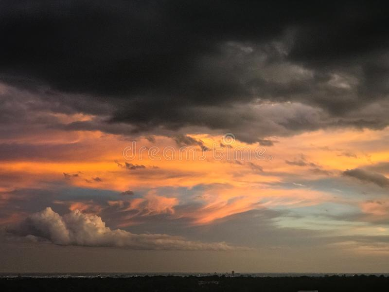 Devilish Storm Clouds with Sunset Over City. A bright colored sunset in background, with dark storm clouds nearby. Made for a dramatic sunset. A hint of blue sky stock photography
