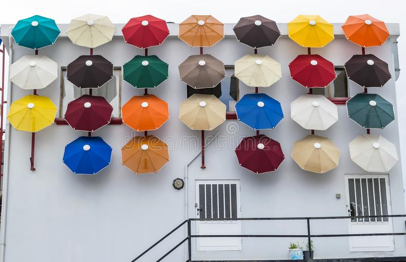 Bright colored umbrellas decorating the wall of the building.  royalty free stock photos