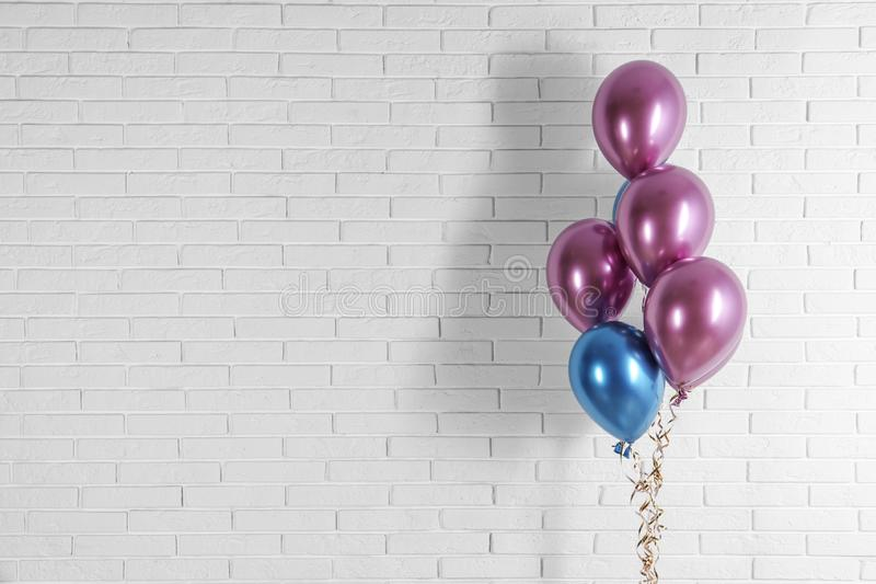Bright colorful balloons near brick wall, space for text. stock images