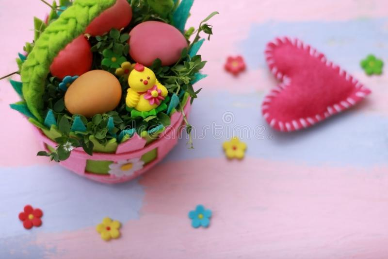 Bright colorful basket of felt with painted eggs and chicken on a pink-blue background. Handmade from felt. Happy Easter greeting stock photo