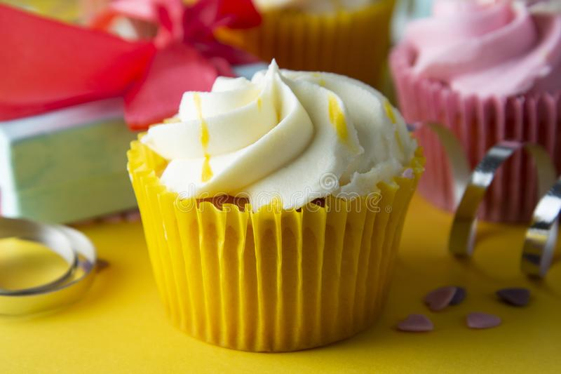 Bright, colorful birthday background with cupcakes, gift boxes, sweets and decorations. Copy space. Yellow background stock photo