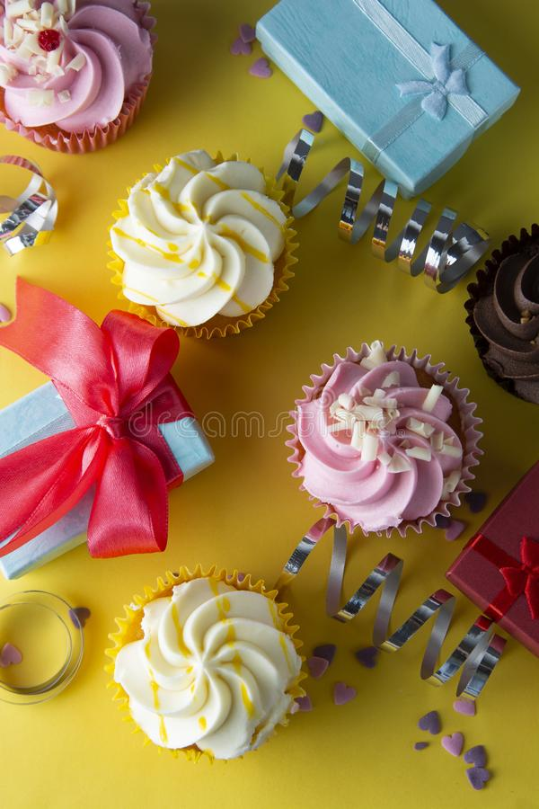 Bright, colorful birthday background with cupcakes, gift boxes, sweets and decorations. Copy space. Yellow background royalty free stock image