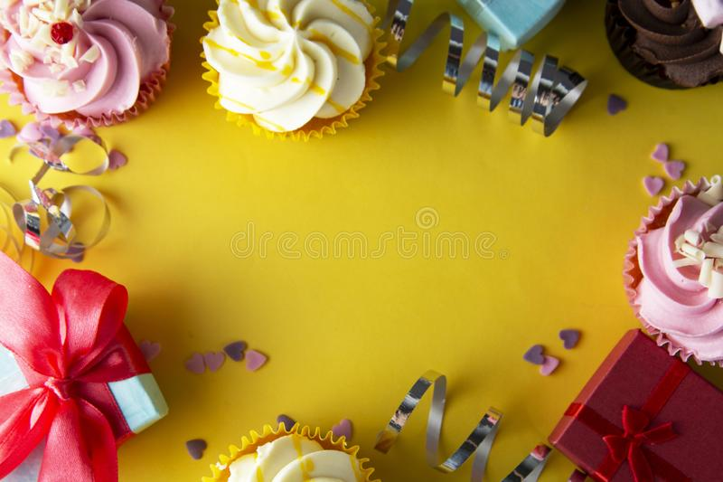 Bright, colorful birthday background with cupcakes, gift boxes, sweets and decorations. Copy space. Yellow background stock images