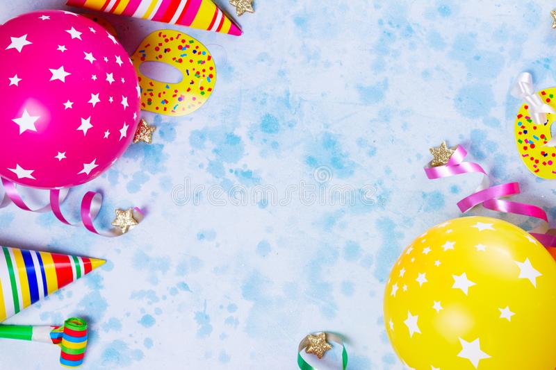 Bright colorful carnival or party scene. Of balloons, streamers and confetti on blue. Flat lay style, birthday or carnival party greeting card with copy space stock image