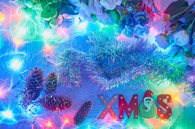 Bright colorful Christmas background with garlands of coniferous cones flowers and the inscription of their tree royalty free stock image