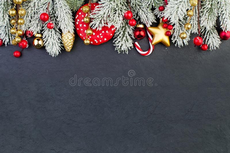 Bright colorful Christmas border with Xmas decor on black background. Green Xmas tree twig, red glass balls, berries, candy food royalty free stock photos