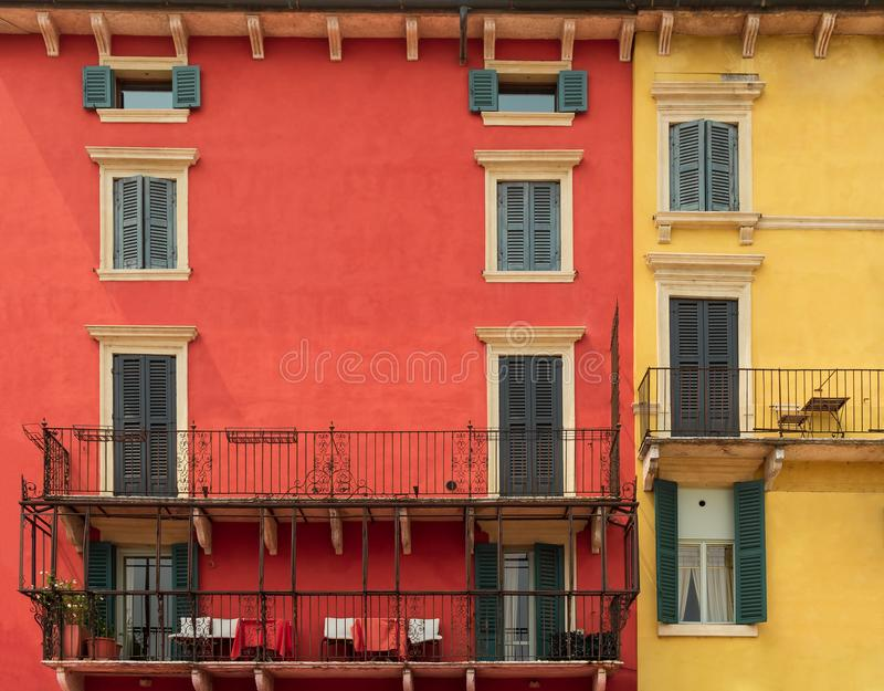 Bright colorful facade of old European building with windows, balconies, tables and chairs and flowers in Verona, Italy royalty free stock photography