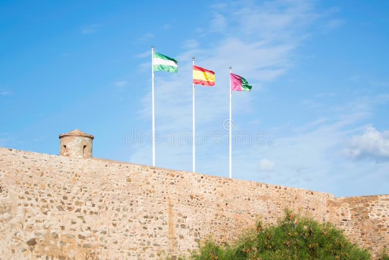 Bright colorful flags over the ancient stone wall of Gibralfaro. Castle Alcazaba de Malaga over the mountain with a bright blue sky at the background on sunny stock image