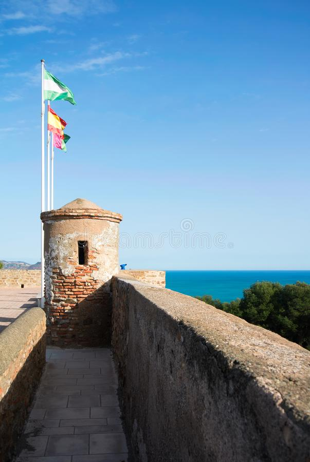 Bright colorful flags over the tover of an ancient stone wall of. Gibralfaro castle Alcazaba de Malaga over the mountain with a bright blue sky and royalty free stock photos