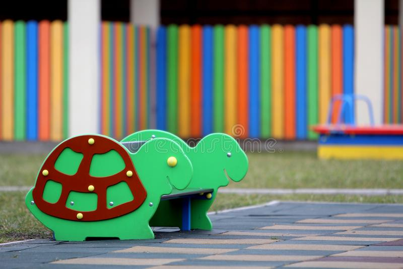 Bright colorful funny bench on nursery playground with soft rubber flooring on bright sunny summer day. Children activities and stock image