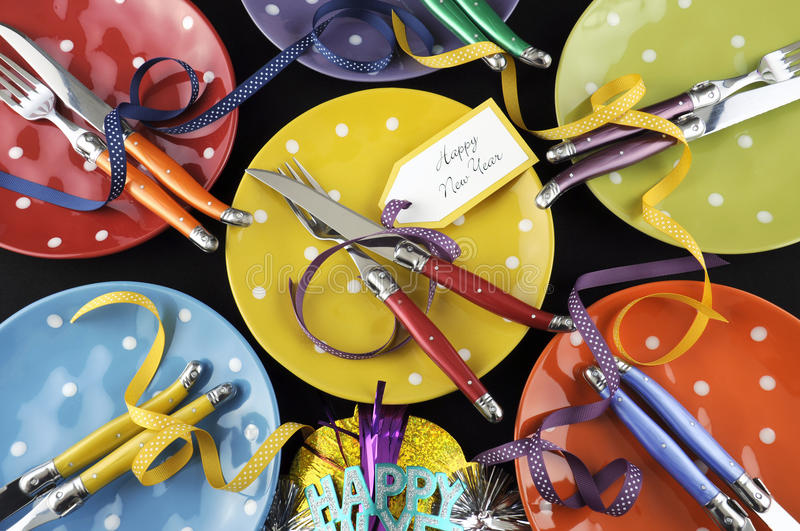 Bright and colorful Happy New Year party dinner table. With red, yellow, orange, blue, green, and purple polka dot plates and cutlery royalty free stock image