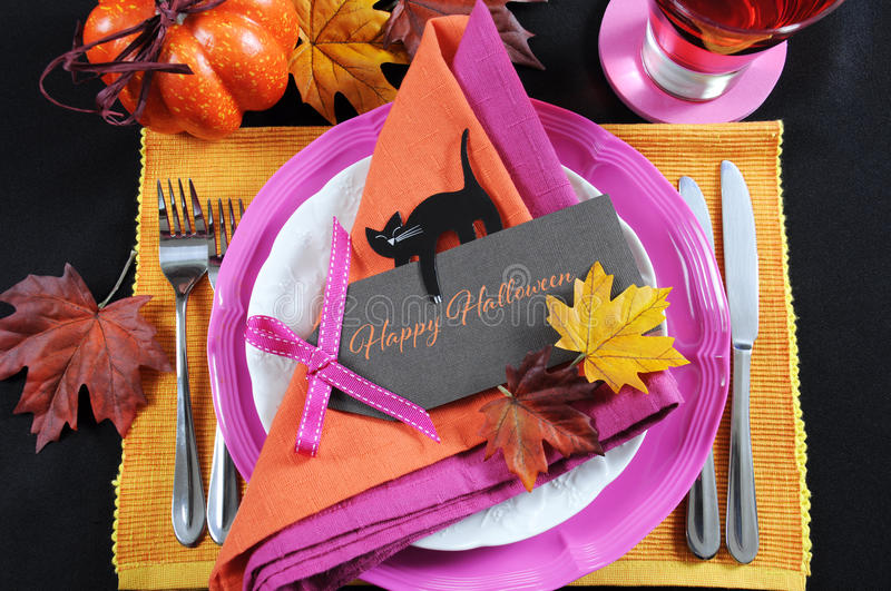 Bright and colorful pink, orange and black modern Happy Halloween table place setting. With greeting tag text message stock photography