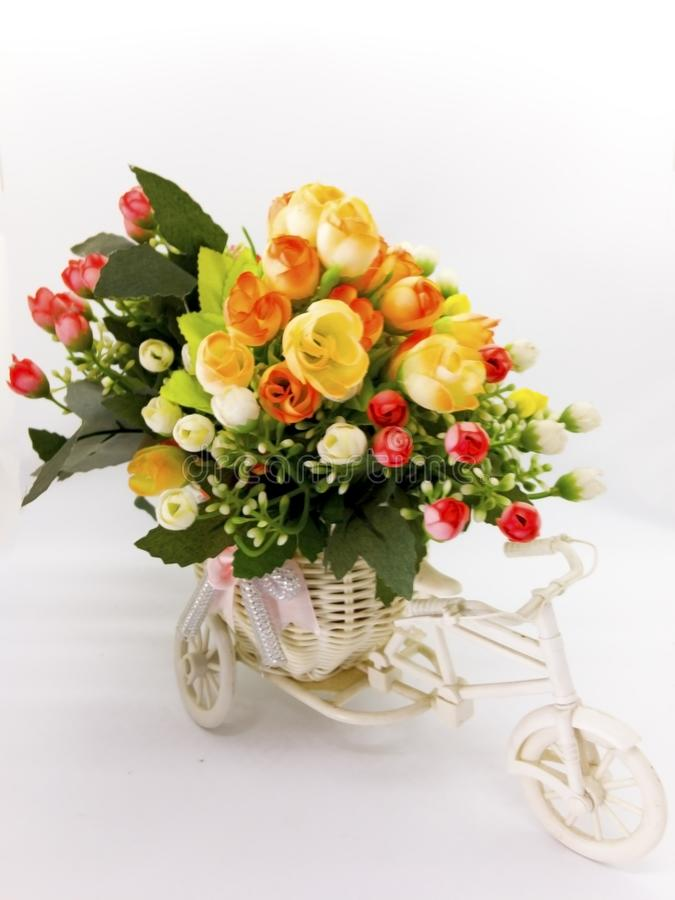 Bright and colorful plastic flower bouquet are in the white bicycle vase, isolated on white background and clipping path. stock photography