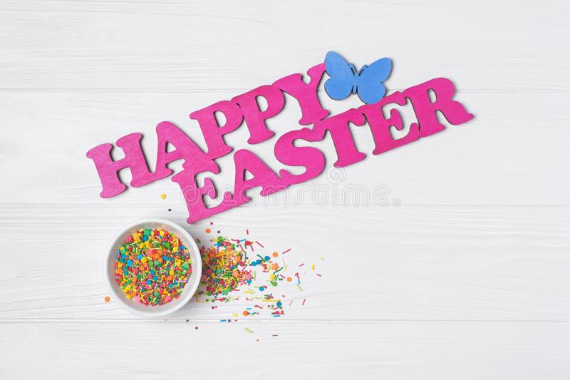 Bright colorful sugar sprinkles or confetti as baking decor with text happy easter. Top view on bright colorful sugar sprinkles or confetti in white bowl as stock images