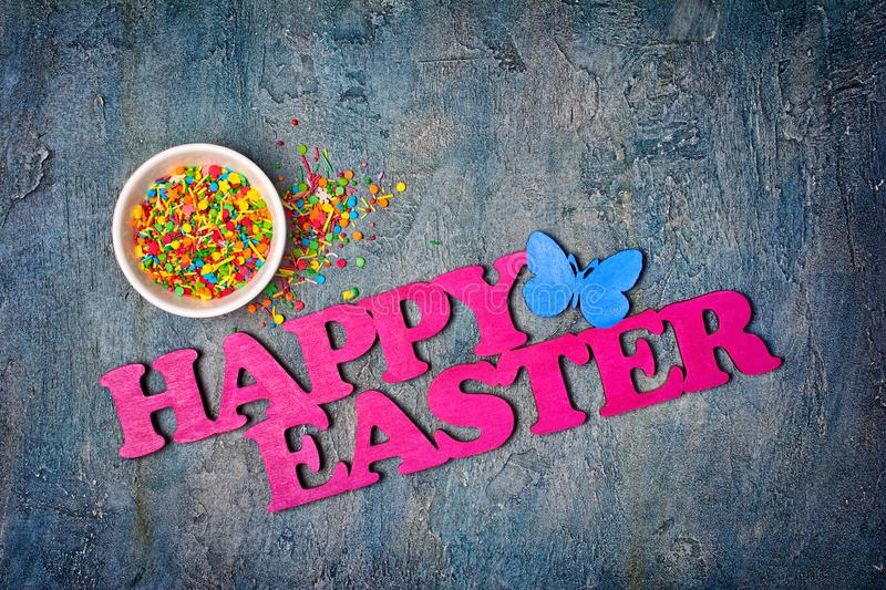 Bright colorful sugar sprinkles or confetti as baking decor with text happy easter. Top view on bright colorful sugar sprinkles or confetti in white bowl as stock image