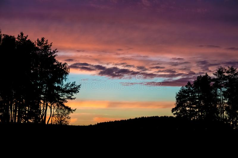 Bright colorful summer sunset. beautiful multi-colored sky. striped clouds royalty free stock photography
