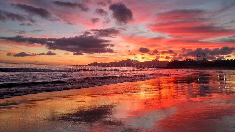 Red sunset over the atlantic ocean in puerto del carmen on lanzarote canary island in spain. Bright colorful sunset on the atlantic ocean coast in the beach of royalty free stock photo